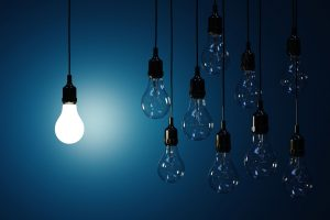 36570046 - 3d render  of hanging light bulbs with glowing one isolated on dark blue background